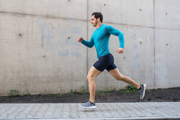 Young man running outdoors in morning stock photo