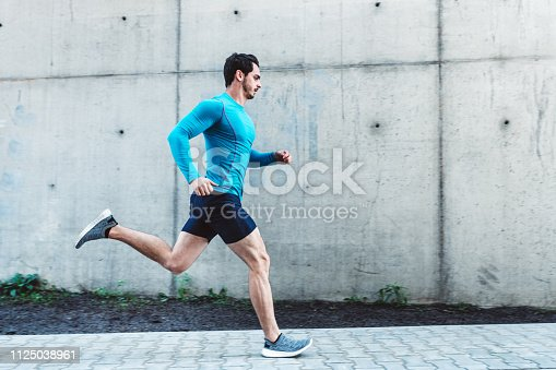 Side view of young man running outdoors in morning. Male athlete in running outfit sprinting outdoors.