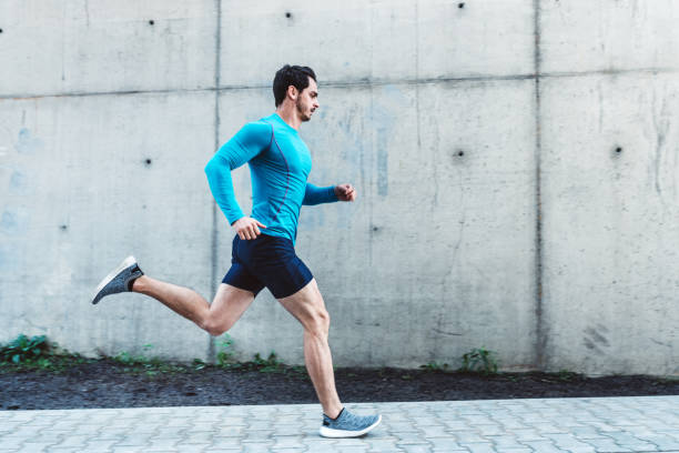 Young man running outdoors in morning Side view of young man running outdoors in morning. Male athlete in running outfit sprinting outdoors. running stock pictures, royalty-free photos & images