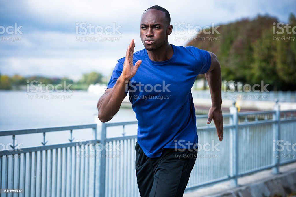 young man running outdoors stock photo