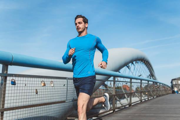Junger Mann läuft über eine Brücke – Foto