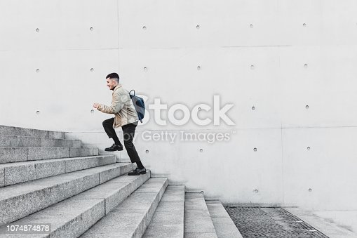 Young man running up steps in urban setting