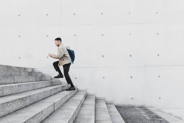 junger mann läuft treppen im städtischen umfeld - treppe außen stock-fotos und bilder