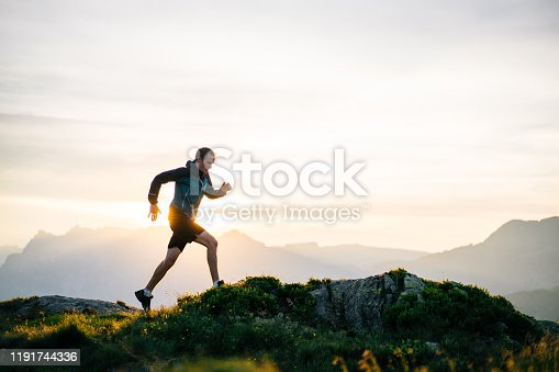 istock Young man runs on mountain ridge at sunrise 1191744336