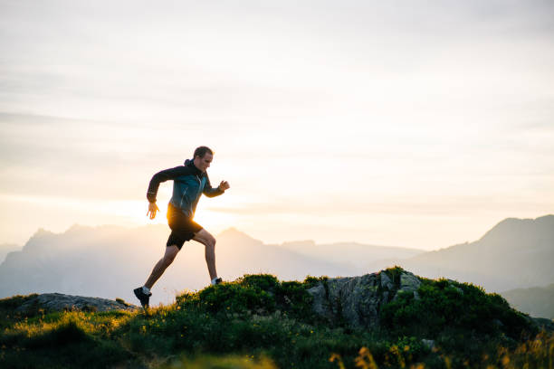 Young man runs on mountain ridge at sunrise He leaps into the morning air exercising stock pictures, royalty-free photos & images