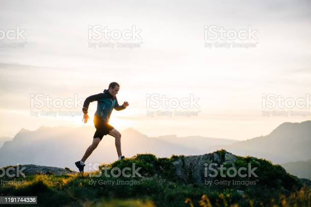 Photo of Young man runs on mountain ridge at sunrise