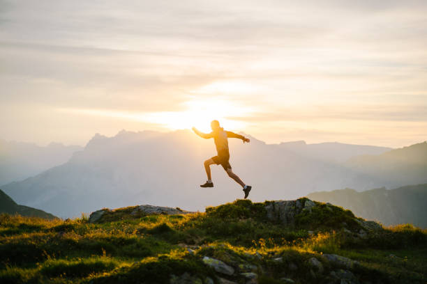 Young man runs on mountain ridge at sunrise stock photo