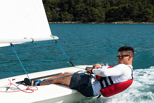 Young man sails a laser class sailing boat International laser class sailing boat with young male boats-man practicing, close-up sailing dinghy stock pictures, royalty-free photos & images