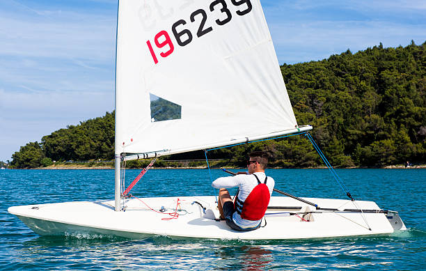 Young man sails a laser class sailing boat Side view of young male boats-man sailing on laser class sailing boat sailing dinghy stock pictures, royalty-free photos & images