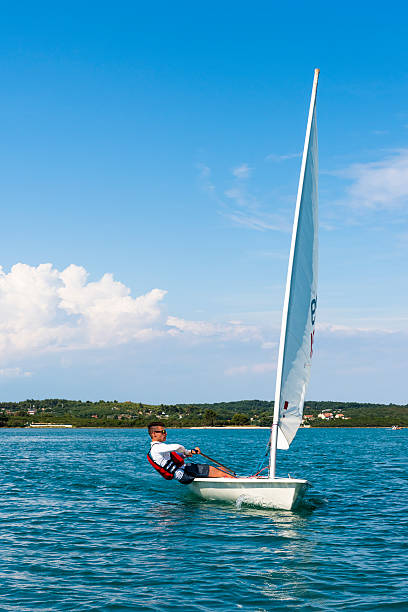 Young Man Sails a Laser Olympic  Class Sailing Boat Side view of young male boats-man sailing on laser class sailing boat sailing dinghy stock pictures, royalty-free photos & images