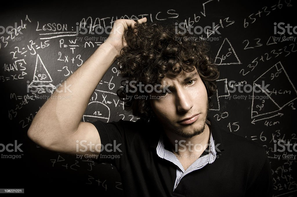 Young Man Scratching Head in Front of Blackboard stock photo