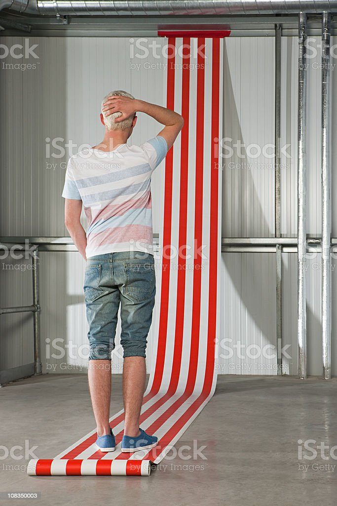 Young man scratching head, striped wallpaper on wall stock photo