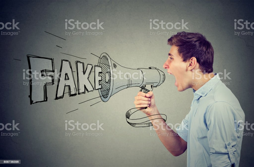 Young man screaming in a megaphone spreading fake news stock photo