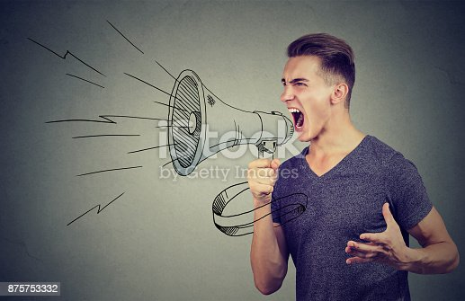 istock Young man screaming into a megaphone making an announcement 875753332