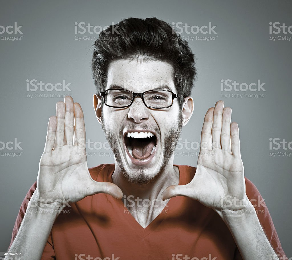 Young man screaming Portrait of young man screaming at the camera. Studio shot, grey background. 20-29 Years Stock Photo