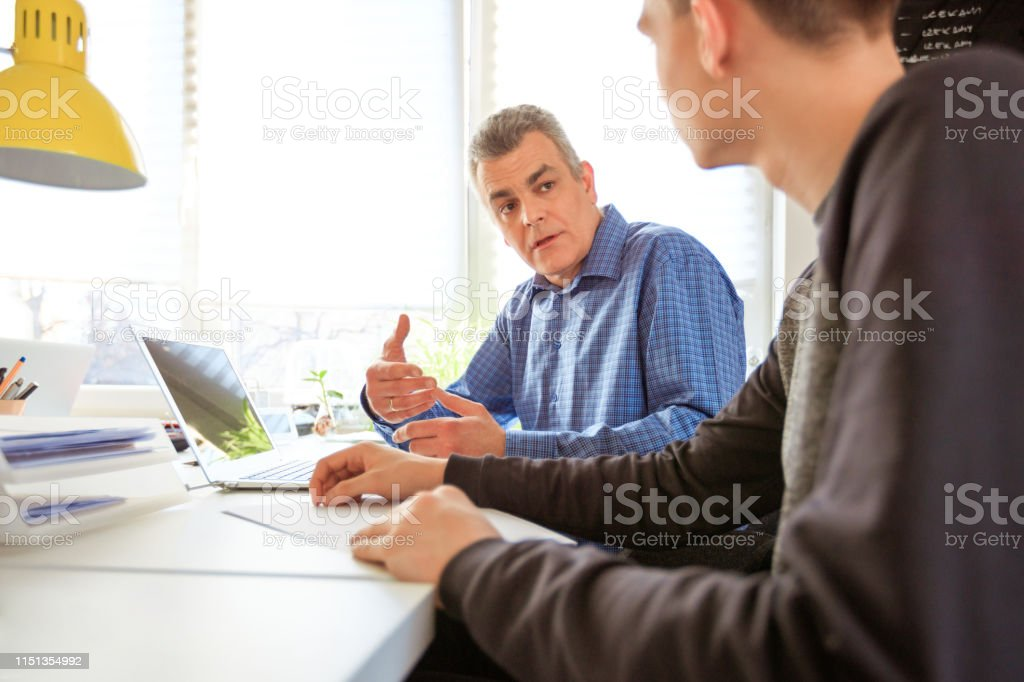 Young man seeking therapist's advice at desk Mental health professional discussing while looking at university student. Young man is seeking for therapist's advice. They are using laptop at desk. 18-19 Years Stock Photo