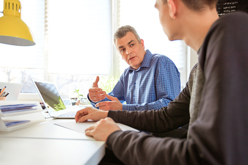 Young Man Seeking Therapists Advice At Desk Stock Photo - Download Image Now