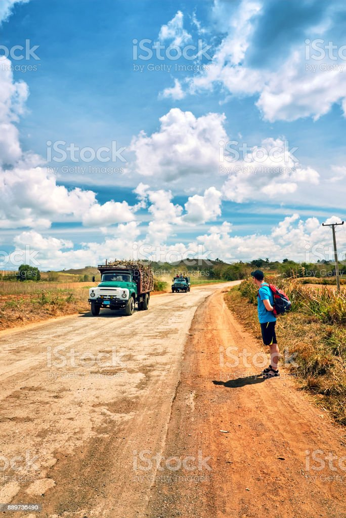 Young man self-locking device backpack points cap old cars locals reed Valley Vinales Road Gulf Mexico  Cuba stock photo