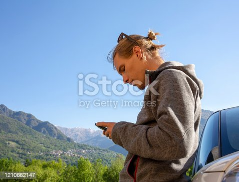 527894422 istock photo Young man sends text from front of vehicle 1210662147
