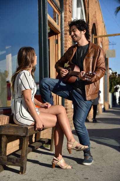 Young man serenading a pretty woman Handsome young man serenading an attractive woman outdoors serenading stock pictures, royalty-free photos & images