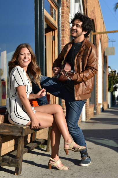 Young man serenading a woman Young man serenading a woman on a bench outdoors serenading stock pictures, royalty-free photos & images