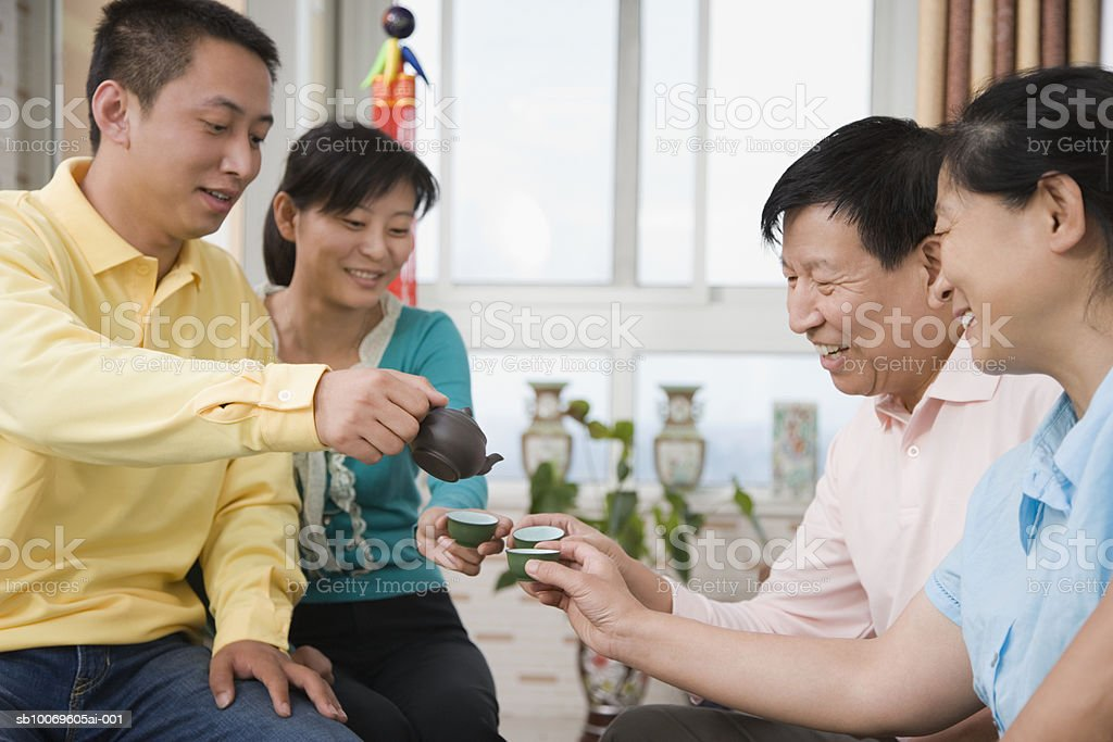 Young man serving tea to guests royalty-free stock photo