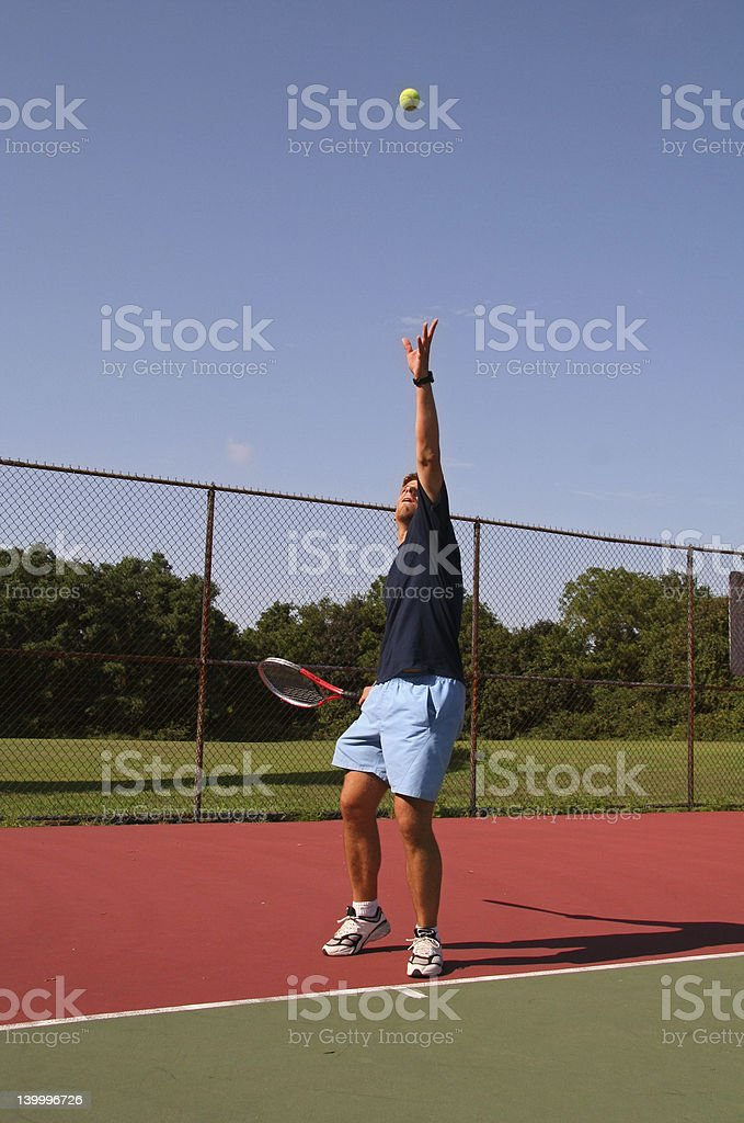 Young man serving tennis ball royalty-free stock photo