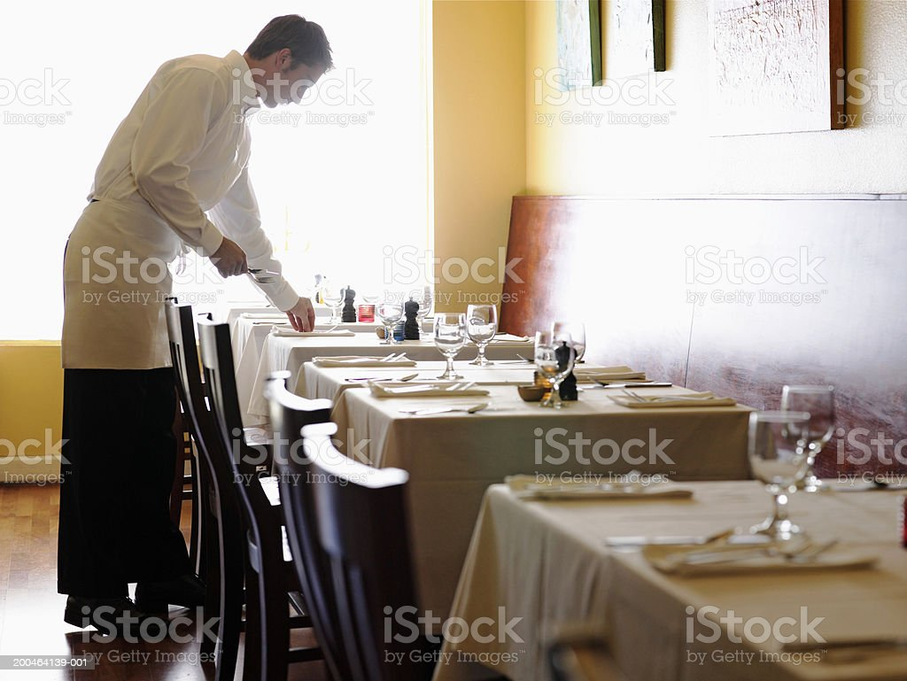 Young man setting tables in restaurant, side view stock photo