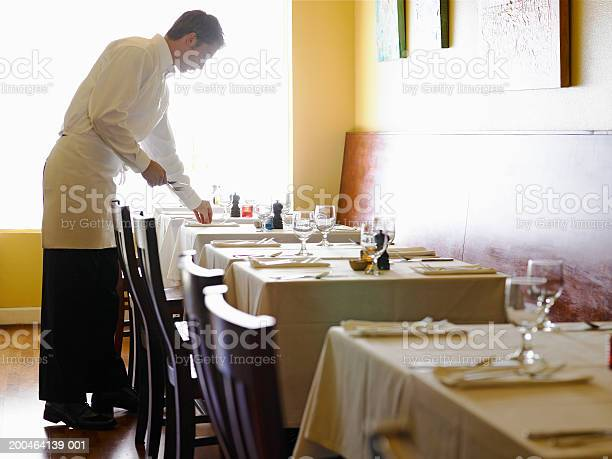 Young Man Setting Tables In Restaurant Side View Stock Photo - Download Image Now