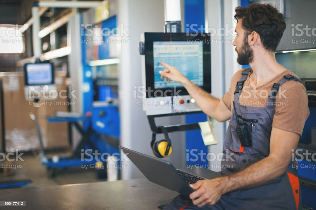 Young man setting the machines in factory stock photo