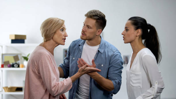 Young man settling conflict between mother and wife, family problems, quarrel stock photo