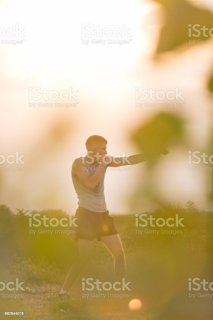 Young man shadow boxing outdoors stock photo