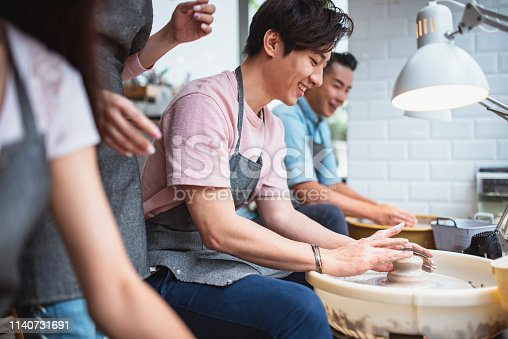 istock Young man shaping clay in a pottery class 1140731691