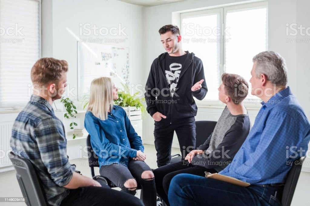 Young man sharing problems during group therapy Young man discussing problems with friends and mental health professional. Mature male therapist is with young university students in lecture hall. They are in group therapy at university. 18-19 Years Stock Photo