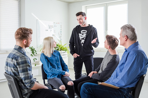 Young Man Sharing Problems During Group Therapy Stock Photo - Download Image Now