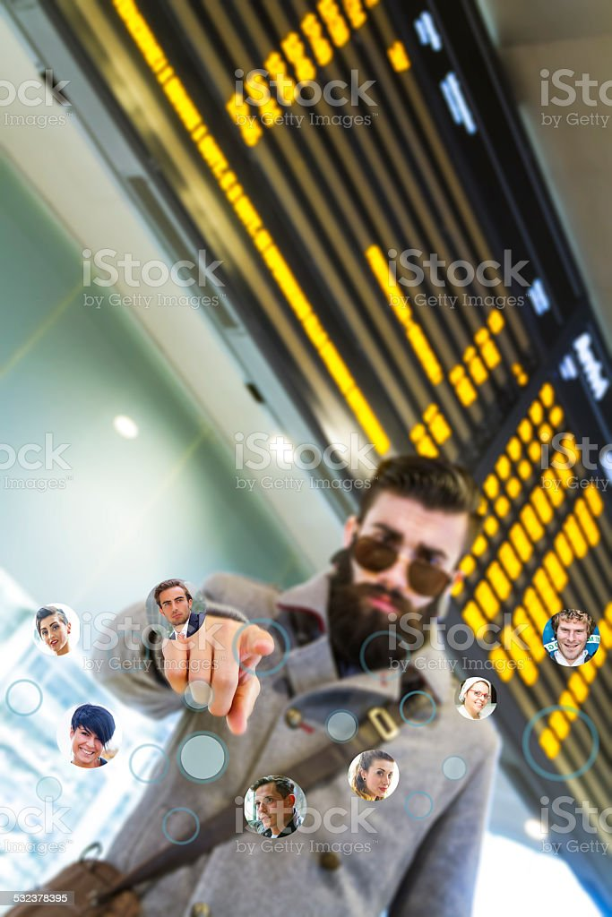 Young man (stylish hipster) sharing trip status with friends stock photo