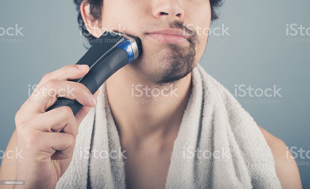 Young man shaving half of his beard stock photo