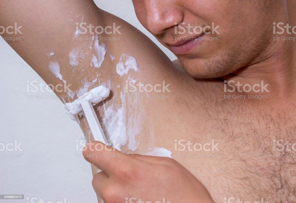 Jeune homme raser son aisselle avec razor - Photo