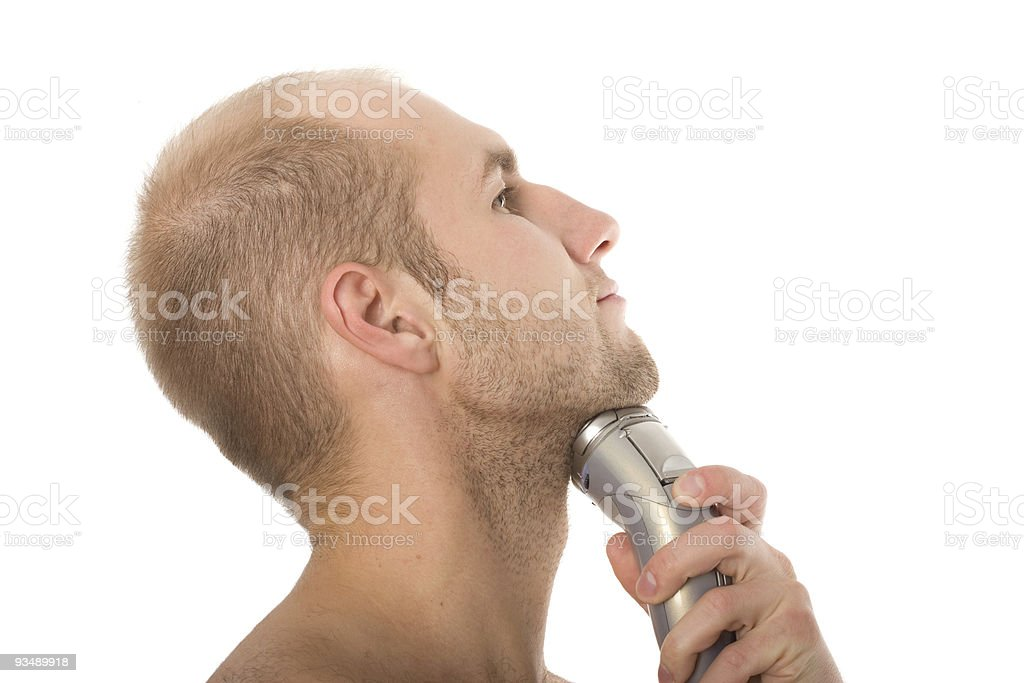 young man shaving his beard off with an electric razor stock photo