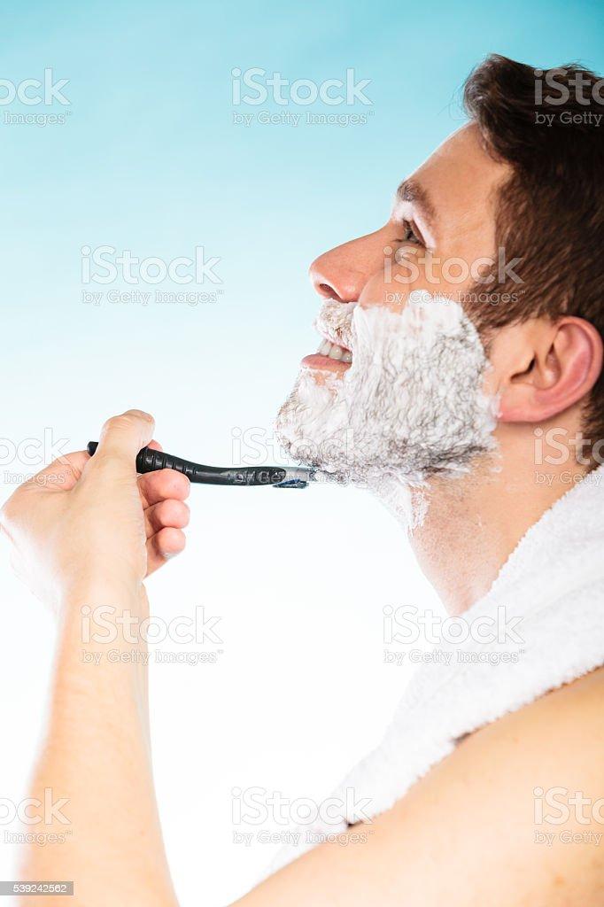 Young man shaving using razor with cream foam. royalty-free stock photo