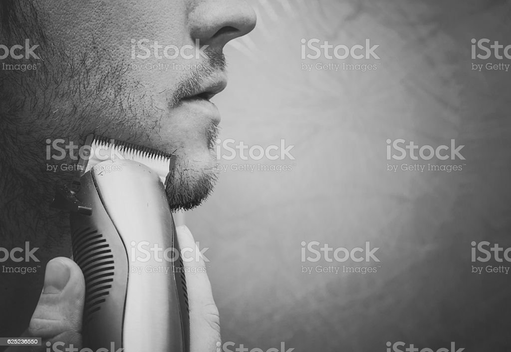 Young man shaving with electric razor. Dark atmosphere with light. stock photo