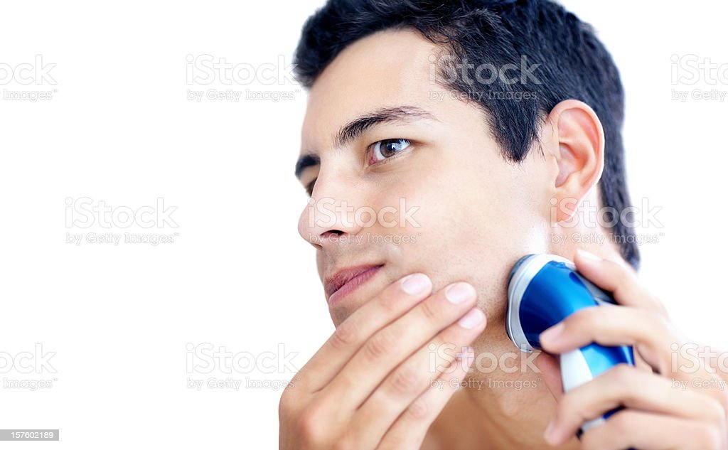 Young man shaving with electric shaver isolated on white stock photo