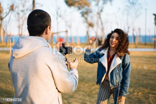 Young man shooting video for young woman