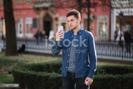 Young man shoots video on smartphome in centre of the city.