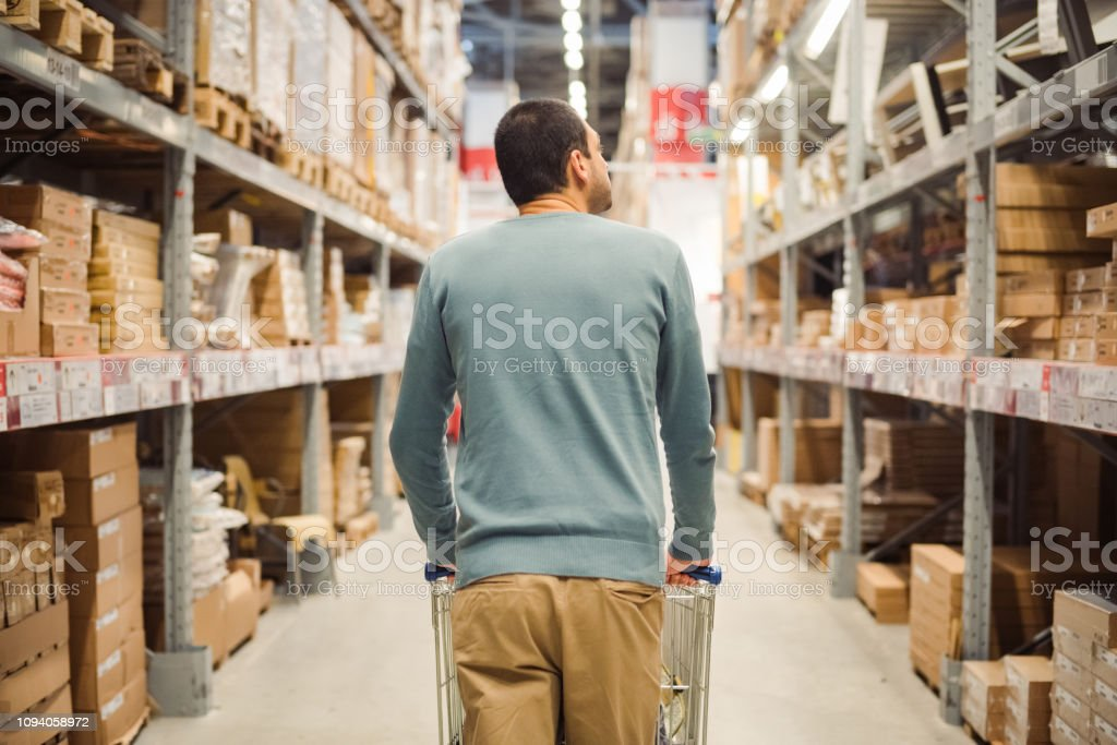 A man with shopping cart in a warehouse