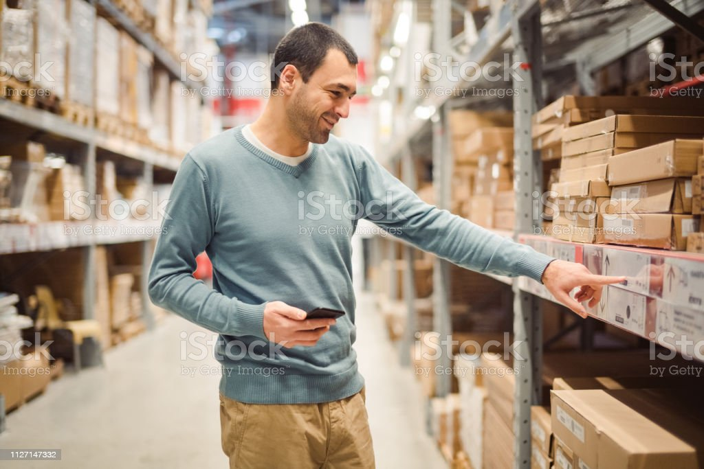 A man with a mobile phone checks prices in a warehouse