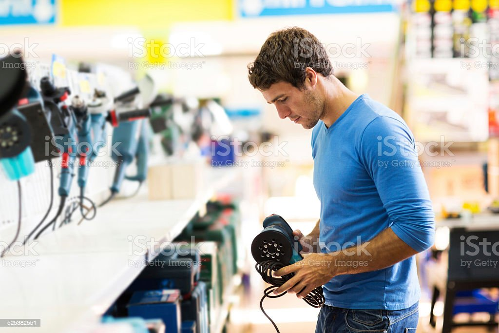 young man shopping for sander in hardware store stock photo