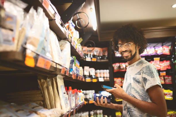 jonge man winkelen in een supermarkt - gemak stockfoto's en -beelden