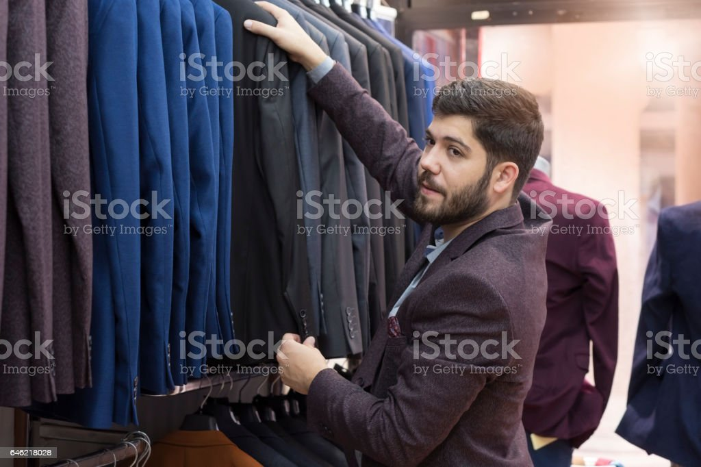Young man shopping in the clothing store stock photo