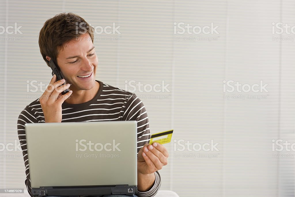 Young man shopping on laptop using a credit card royalty-free stock photo